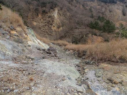 明礬温泉の野湯 泥湯の周りは硫黄成分で山肌の色が変わっています
